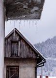 Icycles sur une grange froide d'eith de jour d'hiver dedans derrière Photographie stock libre de droits