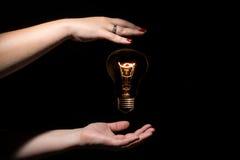 Idé och framgångbegrepp Glödande ljus kula utan trådar mellan kvinnlighänder på svart bakgrund Royaltyfri Bild