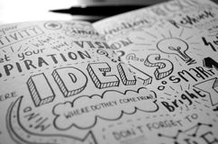 `-IDÉ` skissar anmärkningar som hand-märkas i anteckningsbok fotografering för bildbyråer