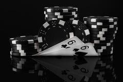Idée blanche noire des jetons de poker et des cartes de tisonnier dans le tisonnier sur un noir Photographie stock