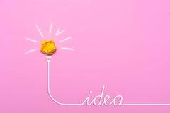 Idée créative de papier chiffonné Une ampoule brûlante sur un fond rose Photos libres de droits