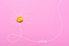 Idée créative de papier chiffonné Une ampoule brûlante sur un fond rose Images stock