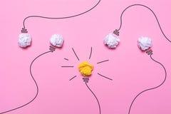 Idée créative de papier chiffonné Une ampoule brûlante sur un fond rose réserve vieux d'isolement par éducation de concept Images libres de droits