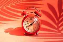 Idée de concepts d'heure d'été avec le réveil et l'ombre tropicale de feuille sur le fond coloré Décoration de vacances image libre de droits