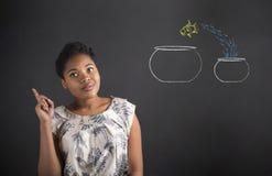 Idée de femme d'afro-américain la bonne avec des poissons roule sur le fond de tableau noir image libre de droits