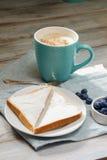Idée de petit déjeuner Tasse avec du café avec des myrtilles, des fleurs et le pain grillé sur la serviette de toile Photo libre de droits