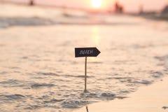 Idée de vacances de vacances - échouez le signe et le coucher du soleil Photographie stock libre de droits