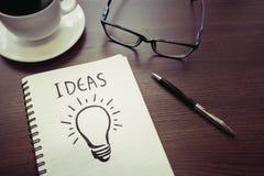 Idéer för affärskreativitetbegrepp teckning för ljus kula på notepaden Royaltyfri Foto