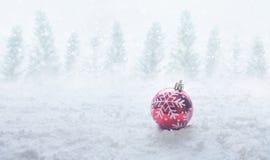 Idéer för julfestivalbegrepp med den röda bollprydnaden på snö royaltyfri bild