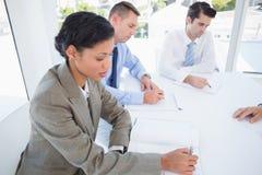 Idées de séance de réflexion d'écriture d'équipe d'affaires en leur bloc-notes Photos stock