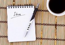Idéia escrita no copo do bloco de notas, da pena e de café Imagens de Stock Royalty Free