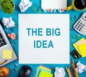 A idéia grande Text o conselho das palavras na mesa com fontes, almofada da tabela do escritório de nota vazia branca, copo, pena Imagens de Stock Royalty Free