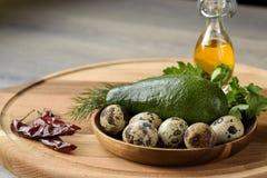 Idén av frukostingredienser för den bakade avokadot: nya avokado, vaktelägg och gräsplaner arkivbild