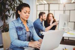 Idérik affärskvinna som använder bärbara datorn på skrivbordet mot coworkers royaltyfri foto