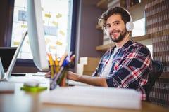 Idérik affärsman som använder datoren medan lyssnande musik Arkivfoton