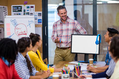 Idérik affärsman som ger presentation till kollegor arkivfoton