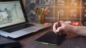 Idérik affärsmanhandstil på den grafiska minnestavlan, medan genom att använda bärbara datorn i regeringsställning lager videofilmer