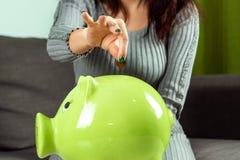 Idérik bakgrund, närbildflickans hand, kastar ett mynt in i spargrisen i form av ett grönt svin Begreppet av besparingen arkivfoton
