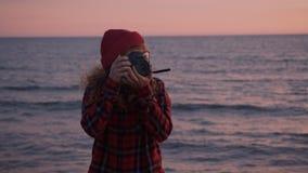 Idérik fotograffreelancerkvinna på stranden lager videofilmer