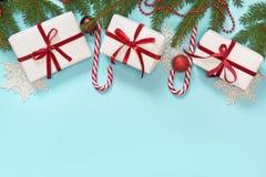 Idérik gräns för jul med den vita och röda dekoren, bollar, gåva, godisrotting, snöflingor på blå bakgrund Lekmanna- lägenhet Top Arkivbild