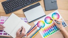 Idérik grafisk formgivare för två kollegor som arbetar på färgval och drar på diagramminnestavlan på arbetsplatsen, färgprovkarta royaltyfri fotografi