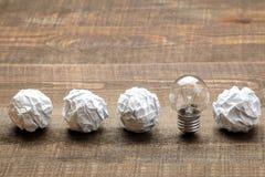 Idérik idé för begrepp Begrepp av den idérika idén Kulor av skrynkligt papper och den ljusa kulan metafor inspiration arkivbild