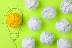 Idérik idé för begrepp Begrepp av den idérika idén Skrynkliga pappers- bollar och målad ljus kula på ljus bakgrund metafor inspi arkivbild