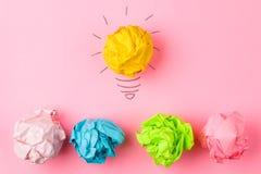 Idérik idé för begrepp Begrepp av den idérika idén Skrynkliga pappers- bollar och målad ljus kula på ljus bakgrund metafor inspi royaltyfri fotografi