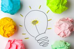 Idérik idé för begrepp Begrepp av den idérika idén Skrynkliga pappers- bollar och målad ljus kula på ljus bakgrund metafor inspi royaltyfria bilder