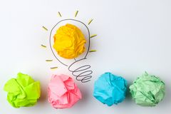 Idérik idé för begrepp Begrepp av den idérika idén Skrynkliga pappers- bollar och målad ljus kula på ljus bakgrund metafor inspi arkivfoto