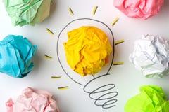 Idérik idé för begrepp Begrepp av den idérika idén Skrynkliga pappers- bollar och målad ljus kula på ljus bakgrund metafor inspi royaltyfri foto