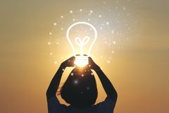 Idérik idé och innovationbegrepp, kvinnahand som rymmer den ljusa kulan på härlig solnedgångbakgrund royaltyfri fotografi