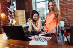 Idérik kvinnlig inredekoratör som arbetar med en kund i hennes kontor som väljer färger för en ny design genom att använda färg royaltyfri foto