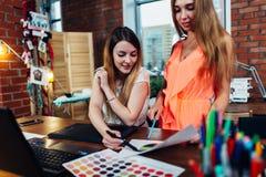 Idérik kvinnlig inredekoratör som arbetar med en kund i hennes kontor som väljer färger för en ny design genom att använda färg arkivbild