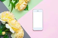 Idérik lägenhet som är lekmanna- av telefonen och gula rosor kopiera avstånd Top beskådar arkivbilder