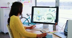 Idérik ledare som använder den grafiska minnestavlan, medan arbeta på den skrivbords- PC:n 4k lager videofilmer