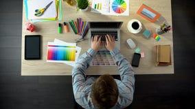 Idérik märkes- maskinskrivning på bärbara datorn som överför konstprojekt till klienten, bästa sikt royaltyfria bilder