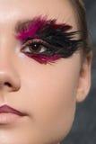 Idérik makeup för skönhet med fjädrar på ögon Fotografering för Bildbyråer