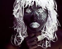 Idérik makeup som den etiopiska maskeringen, vit modell på slut för svart framsida upp, halloween fasa Arkivbild