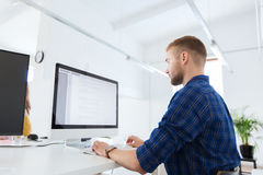 Idérik man eller programmerare med datoren på kontoret Arkivbilder