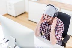 Idérik man med hörlurar som lyssnar till musik på hans dator fotografering för bildbyråer