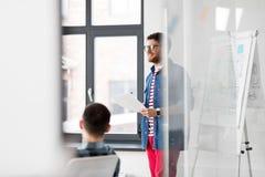 Idérik man med legitimationshandlingar på kontorspresentationen Fotografering för Bildbyråer