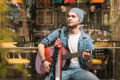 Idérik manlig gitarrist som introducerar sång, innan att sjunga royaltyfri bild