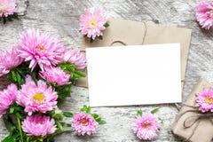 Idérik orientering med det tomma vita greeeting kortet, asterblommor, gåvaasken och blommaknoppar Royaltyfria Bilder