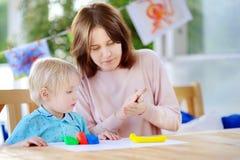 Idérik pojke som spelar med färgrik modellera lera på dagiset royaltyfria bilder