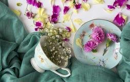 Idérik sammansättning med koppen och blommor arkivfoton