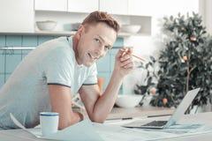 Idérik smart man som ler och står mitt emot bärbara datorn royaltyfria bilder