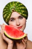 Idérik stående av en kvinna med en vattenmelon på hennes huvud och i hennes händer Vit bakgrund royaltyfri fotografi