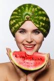 Idérik stående av en kvinna med en vattenmelon på hennes huvud och i hennes händer Vit bakgrund royaltyfri bild
