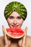 Idérik stående av en kvinna med en vattenmelon på hennes huvud och i hennes händer Vit bakgrund royaltyfri foto